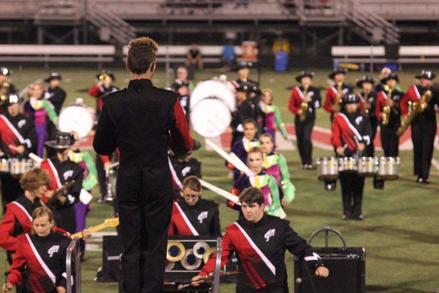 Joel Linebach conducts the 2016 Lancer Marching Band from the drum major podium.