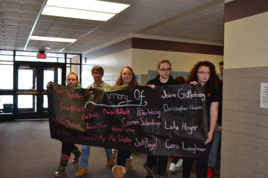 Students silently walk through the halls of GMHS carrying a banner which memorialized the victims of the Parkland shooting.