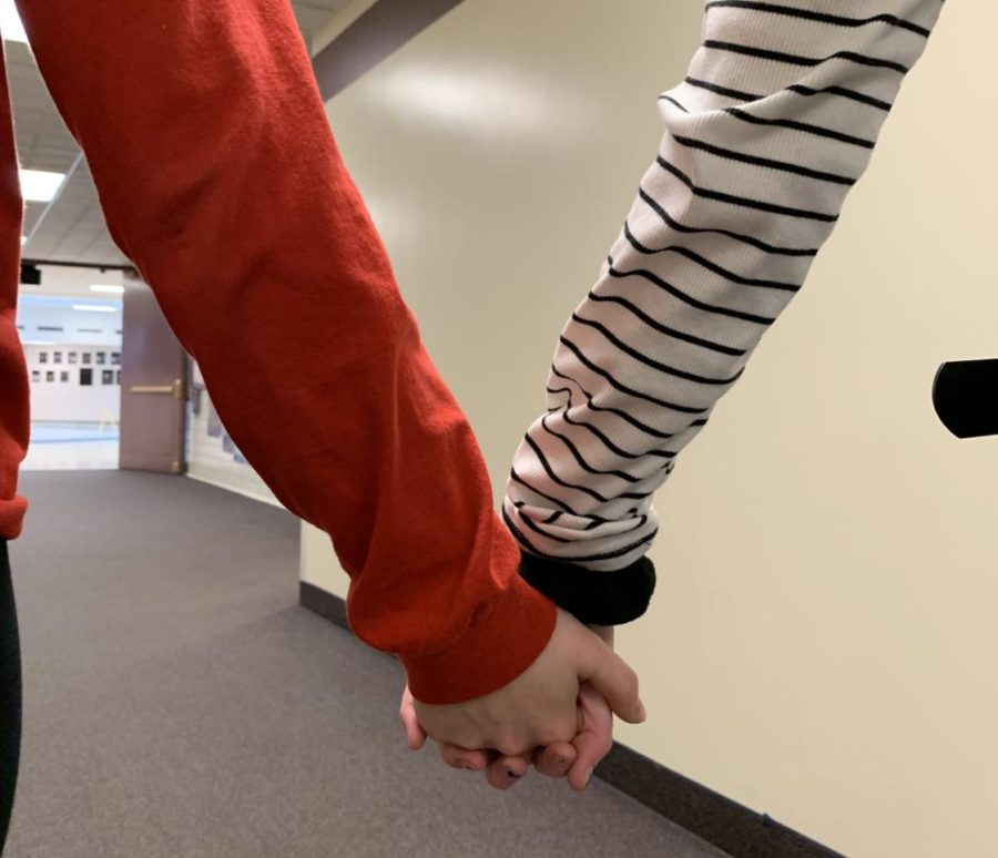 A couple holds hands walking down the hall.