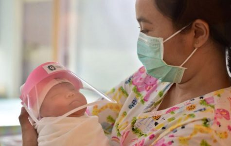 A new infant in Bangkok wears a face shield to help stop the spread of COVID-19.