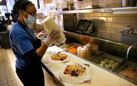Most food service employees are required to wear face masks at work. General manager Sandrea Smith at Seoul Taco prepares a steak burrito for hospital workers April 16, 2020, as part of the Off Their Plate  initiative.(Antonio Perez / Chicago Tribune)