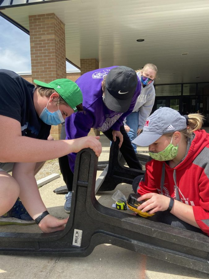 Logan Mitchell, Tanner Daniels, Megan Fay, and Sarah Thomas build a bench which was installed outside the athletic entrance of GMHS.